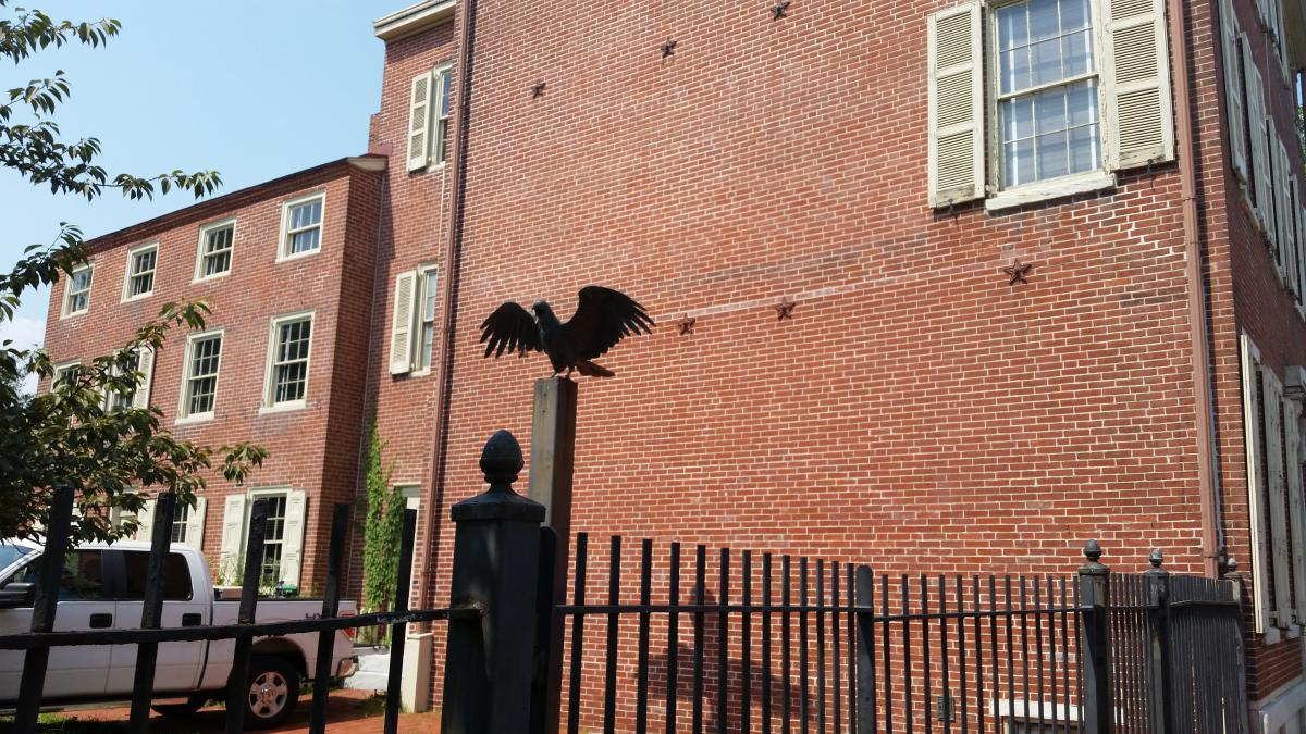 A Sculpture of a Raven next to The Edgar Allan Poe House in Philadelphia